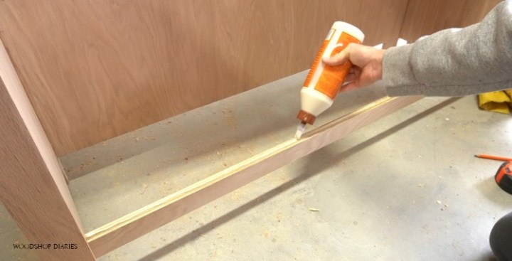 Applying glue to assemble bottom panel into DIY L shaped desk right side cabinet