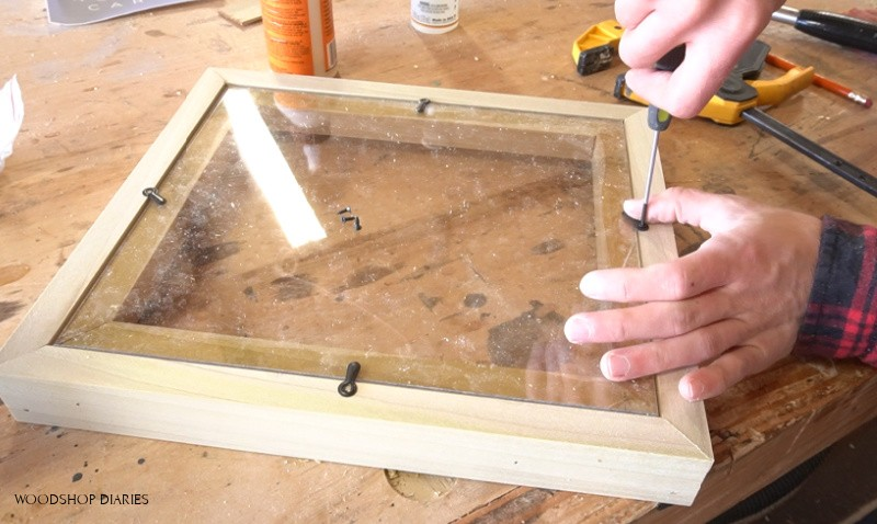 Screwing turn buttons onto back of easy DIY floating picture frame