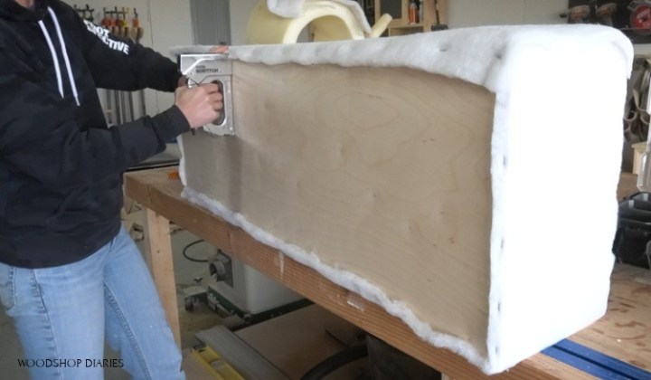 Stapling batting onto bottom of upholstered storage bench