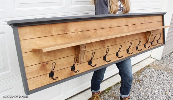 Angled view of Shara holding DIY coat rack with shelf in front of garage door