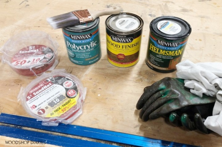 Materials needed to stain wood--stain, rag, gloves, sandpaper, brush, clear coat poly