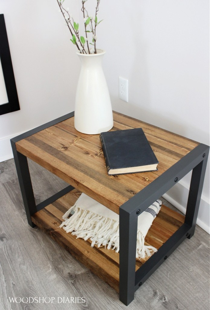 Angled view of DIY black and wood end table with timber screws on sides. Black frames and wood top and bottom shelves with vase and book on top