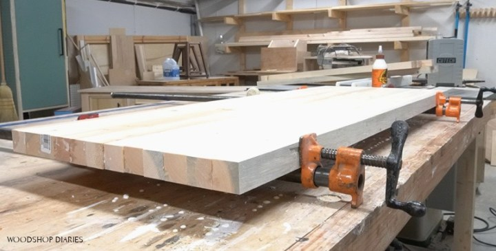 Panel in pipe clamps on workbench being glued together