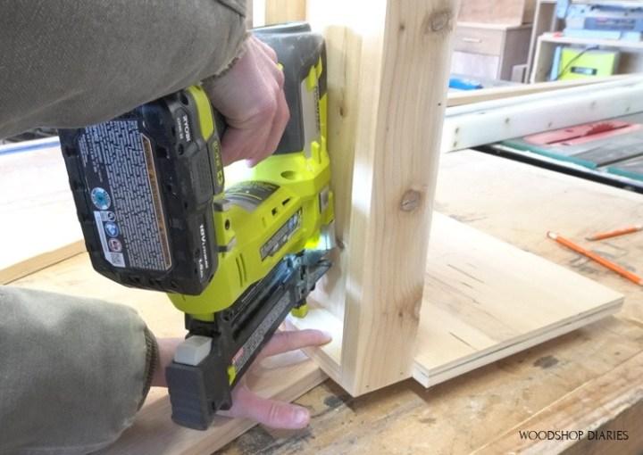 Using nail gun to secure bottom shelf to ladder sides