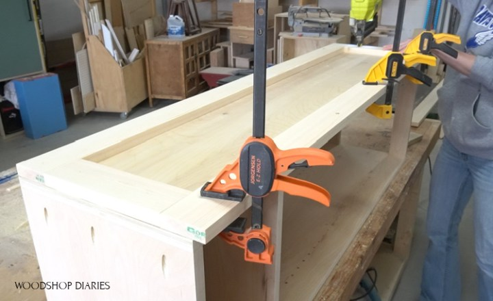 Brad nailing side panel trim onto DIY pantry cabinet