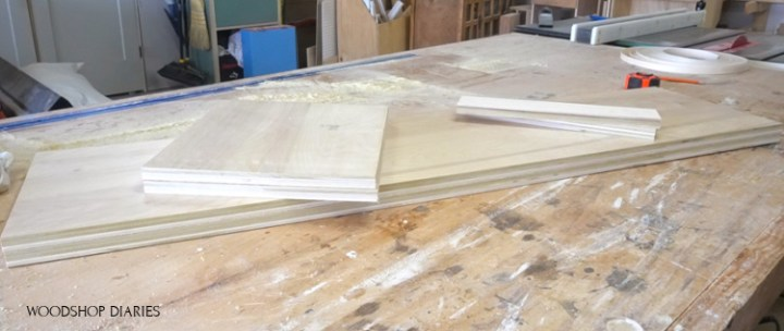 plywood pieces laid out on workbench to build linen cabinet carcass