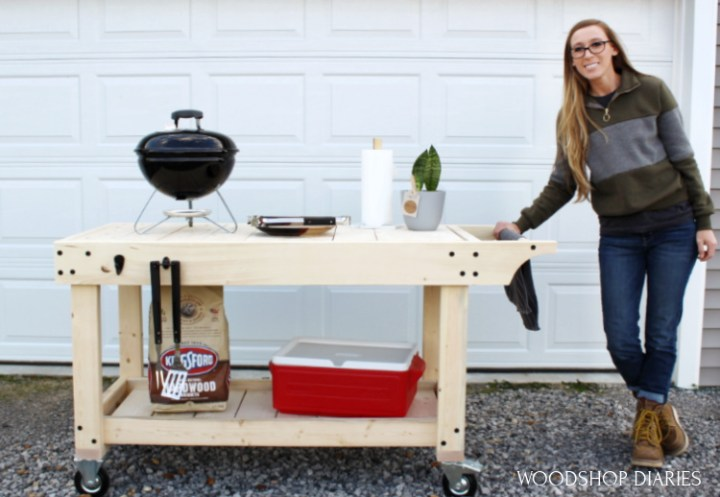 Shara holding onto handle of mobile DIY grill cart with portable grill on top and cooler on bottom