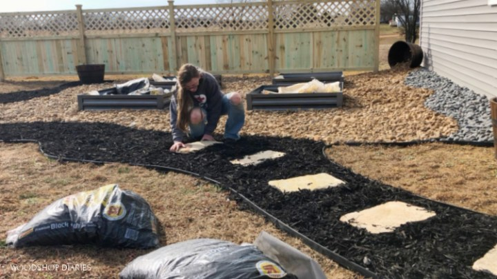 Installing stepping stones in black mulch walkway of backyard makeover