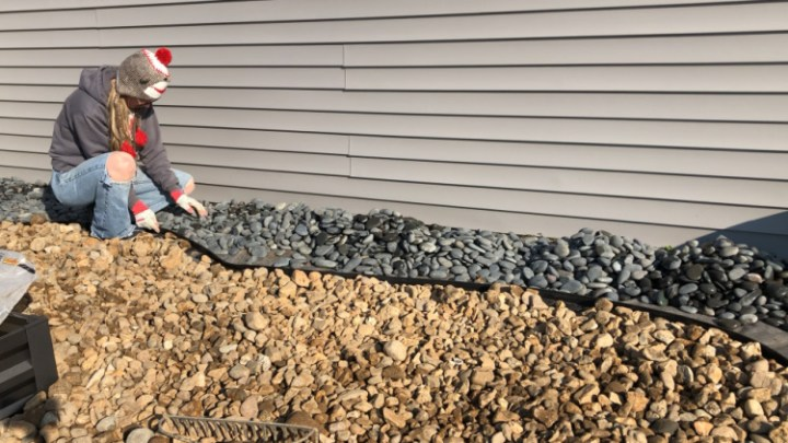 Shara spreading Mexican beach pebbles next to house