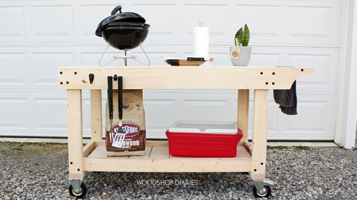 BBQ prep table on wheels with grill on top and cooler below and bag of charcoal ready to cook