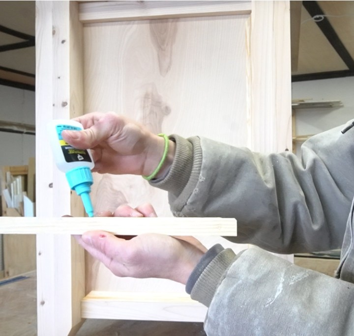 Shara using RapidFuse to attach trim pieces to side of DIY file cabinet