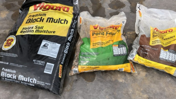 Black mulch, pond pebbles, and Mexican beach pebble bags laying side by side on ground