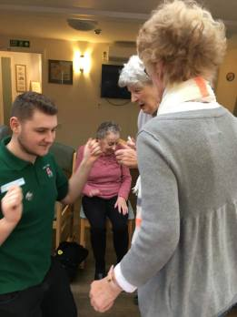 Zak, who is doing work experience at Woodspring, shows the ladies how to dance.