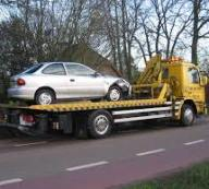 silver car on yellow towing truck