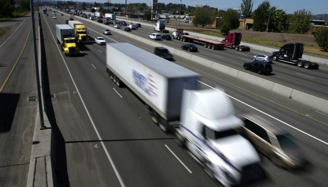 Semi-trucks drive down I-5 through Fife, Washington