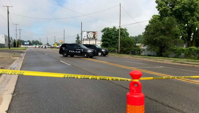 Police tape and police cruisers in front of Chicago Drive crash scene