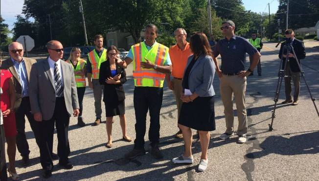 Gretchen Whitmer turns to listen to man in traffic vest near Ferrysburg bridge with people gathered around