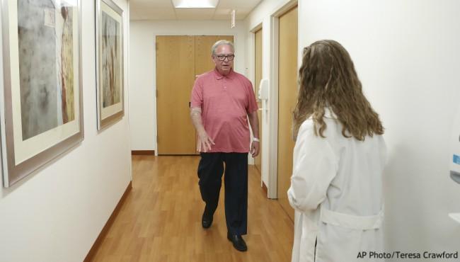Tom Doyle walks down a hospital hall to his doctor