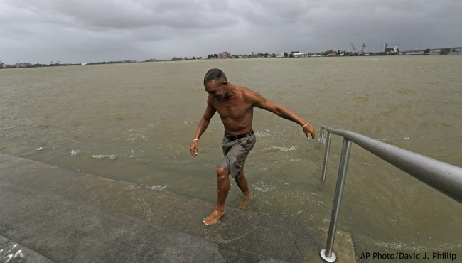 Ray Leon walks up steps after swimming in the Mississippi River, Friday, July 12, 2019, in New Orleans, ahead of Tropical Storm Barry. Barry could harm the Gulf Coast environment in a number of ways. But scientists say it's hard to predict how severe the damage will be. (AP Photo/David J. Phillip)