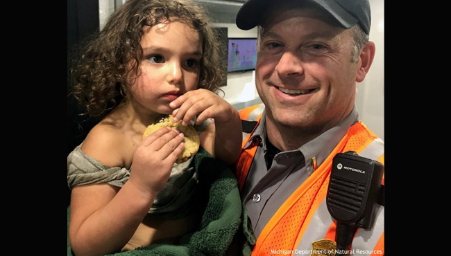 Male officer holding girl with cookie