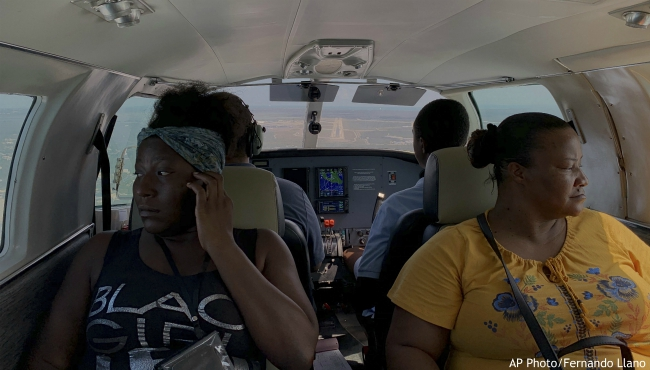 """Dimple Lightbourne, left, and her mother Carla Ferguson sit in a plane as it approaches to land in Nassau after they were evacuated from Abaco Island, in the Bahamas, Monday, Sept. 9, 2019. """"We don't know where we're going to stay,"""" said Ferguson, a 51-year-old resident of Treasure Cay. (AP Photo/Fernando Llano)"""