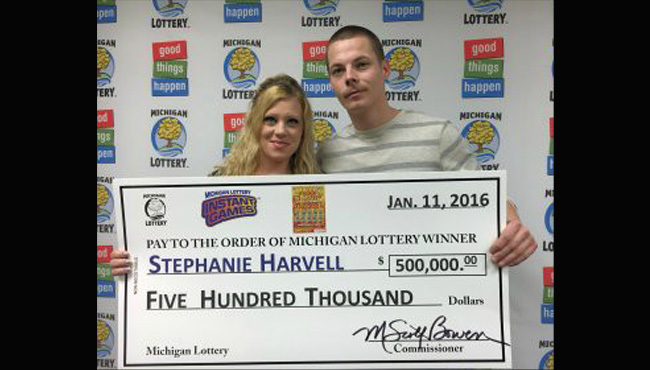 Stephanie Harvell holding check with husband