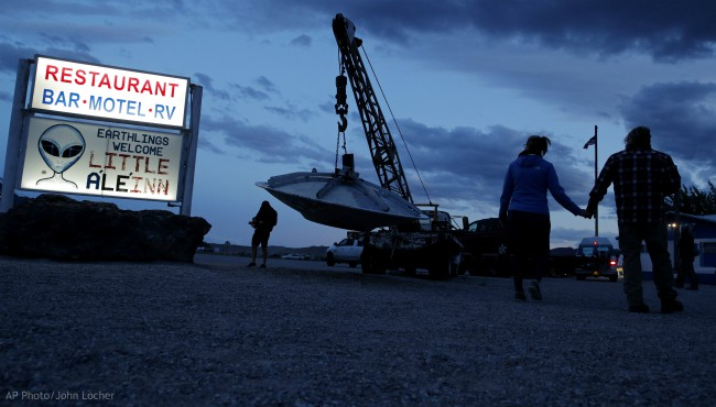 """People walk near the Little A'Le'Inn during an event inspired by the """"Storm Area 51"""" internet hoax, Thursday, Sept. 19, 2019, in Rachel, Nev. (AP Photo/John Locher)"""