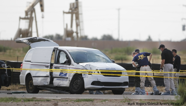 Authorities look at a U.S. Mail vehicle, which was involved in Saturday's shooting, outside the Cinergy entertainment center Sunday, Sept. 1, 2019, in Odessa, Texas. (Mark Rogers/Odessa American via AP)