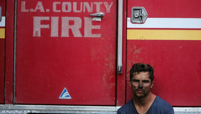 Los Angeles County Firefighter Collin Bashara takes rest with his fire truck in Los Angeles, Monday, Oct. 28, 2019. (AP Photo/Ringo H.W. Chiu)