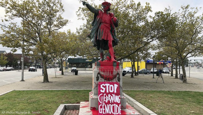 "A sign reading ""stop celebrating genocide"" sits at the base of a statue of Christopher Columbus on Monday, Oct. 14, 2019, in Providence, R.I., after it was vandalized with red paint on the day named to honor him as one of the first Europeans to reach the New World. (AP Photo/Michelle R. Smith)"