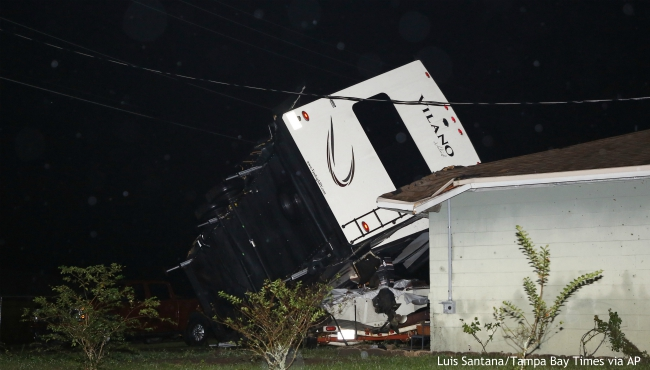 A camper rests on top of a boat trailer and the corner of a home as Tropical Storm Nestor passed the area on Saturday, Oct. 19, 2019 in Kathleen, Fla. Nestor was downgraded Saturday after it spawned a tornado that damaged several homes. (Luis Santana/Tampa Bay Times via AP)