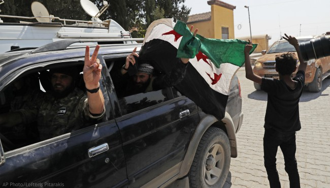 Members of Turkey-backed Syrian National Army (former FSA) flash the V-sign as they drive back to Turkey after they went in for some time on inspection according to the Turkish police entourage in the same area at the border between Turkey and Syria, in Akcakale, Sanliurfa province, southeastern Turkey, Wednesday, Oct. 9, 2019. (AP Photo/Lefteris Pitarakis)