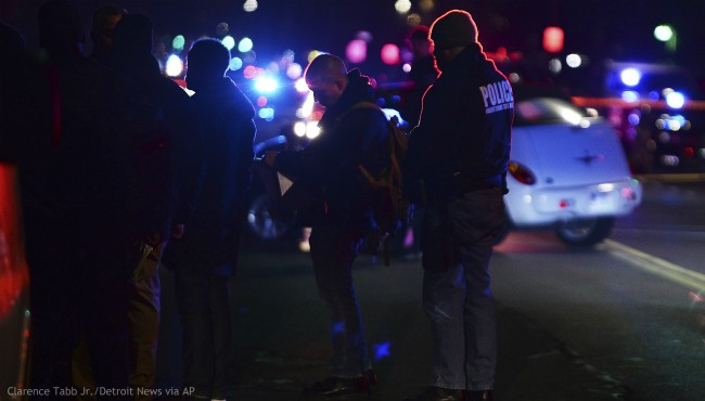 Detroit Police officers gather on the corner of Wyoming and Chippewa streets where one officer was fatally shot and another was wounded while responding to a home invasion on Detroit's West Side, late Wednesday, Nov. 20, 2019. (Clarence Tabb Jr./Detroit News via AP)