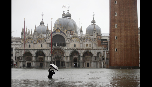 A photographer takes pictures in a flooded St. Mark's Square, in Venice, Italy, Tuesday, Nov. 12, 2019. (AP Photo/Luca Bruno)