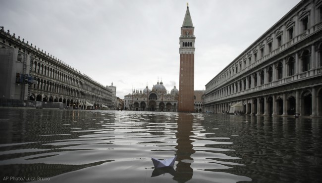A boat made with a paper sheet floats in a flooded St. Mark's Square at Venice, Friday, Nov. 15, 2019. (AP Photo/Luca Bruno)