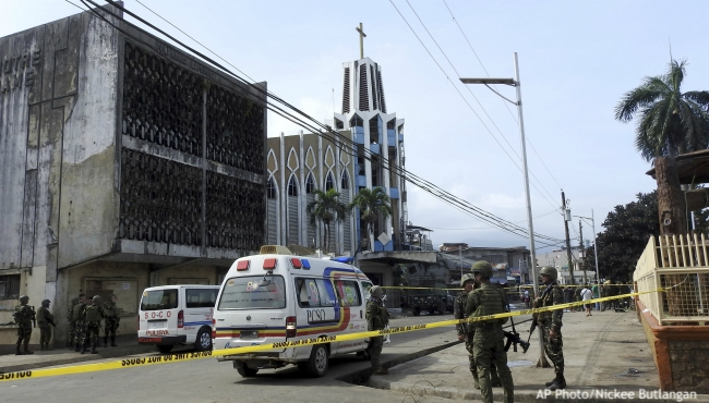 FILE - In this Jan. 27, 2019, file photo, police investigators and soldiers attend the scene after two bombs exploded outside a Roman Catholic cathedral in Jolo, the capital of Sulu province in southern Philippines. Two suicide attackers detonated bombs during a Mass in a Roman Catholic cathedral on the largely Muslim island of Jolo, killing 23 and wounding about 100. (AP Photo/Nickee Butlangan, File)