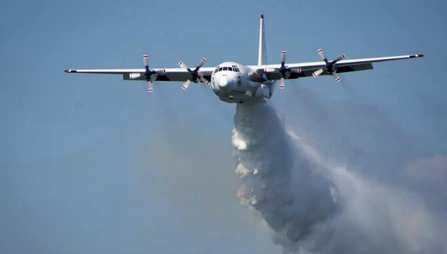 "In this undated photo released from the Rural Fire Service, a C-130 Hercules plane called ""Thor"" drops water during a flight in Australia. (RFS via AP)"