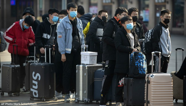 Travelers wear face masks as they stand outside the Beijing Railway Station in Beijing, Friday, Jan. 31, 2020. (AP Photo/Mark Schiefelbein)