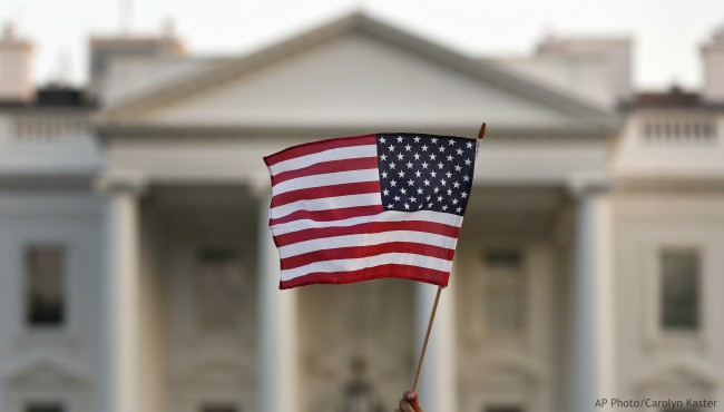 In this Sept. 2017 file photo, a flag is waved outside the White House, in Washington. (AP Photo/Carolyn Kaster)