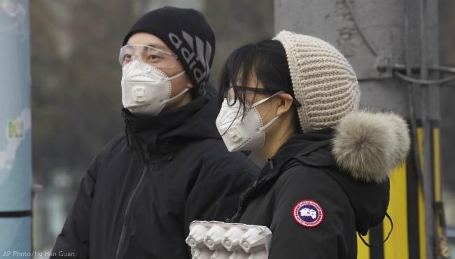 Residents wearing masks wait at a traffic light in Beijing, China Thursday, Feb. 13, 2020. (AP Photo/Ng Han Guan)