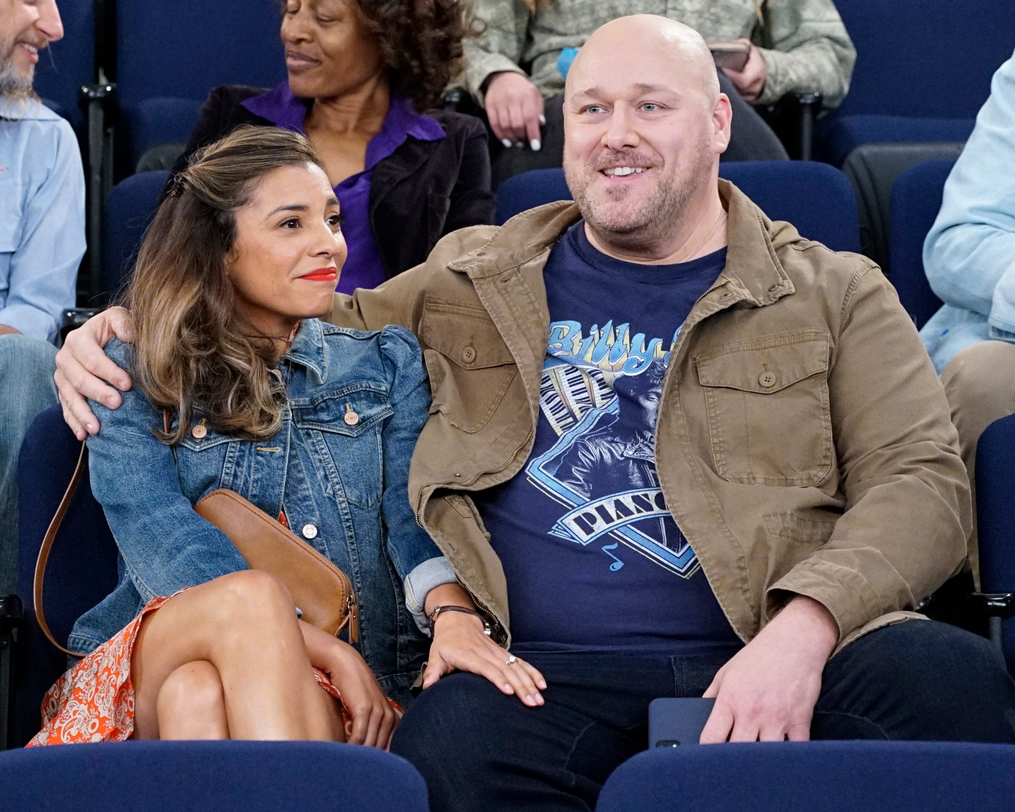 Will Sasso and Christina Vidal Mitchell sitting side by side with arms wrapped around each other watching an event on united we fall