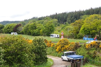 Over the A9 to the car park, maintenance crew in foreground in attendance at the broch
