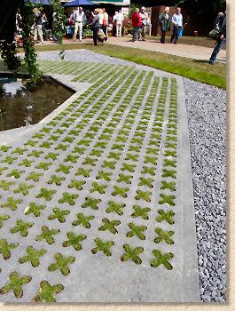 een kruissteek-idee van beton waar gras tussen groeit...