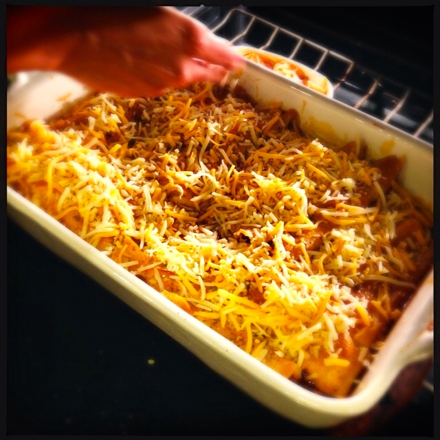 Adding cheese to the enchiladas