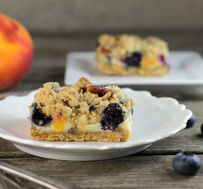 Blueberry peach crumble bars... delicious summer fruit baked between two layers of sweet buttery crumble.