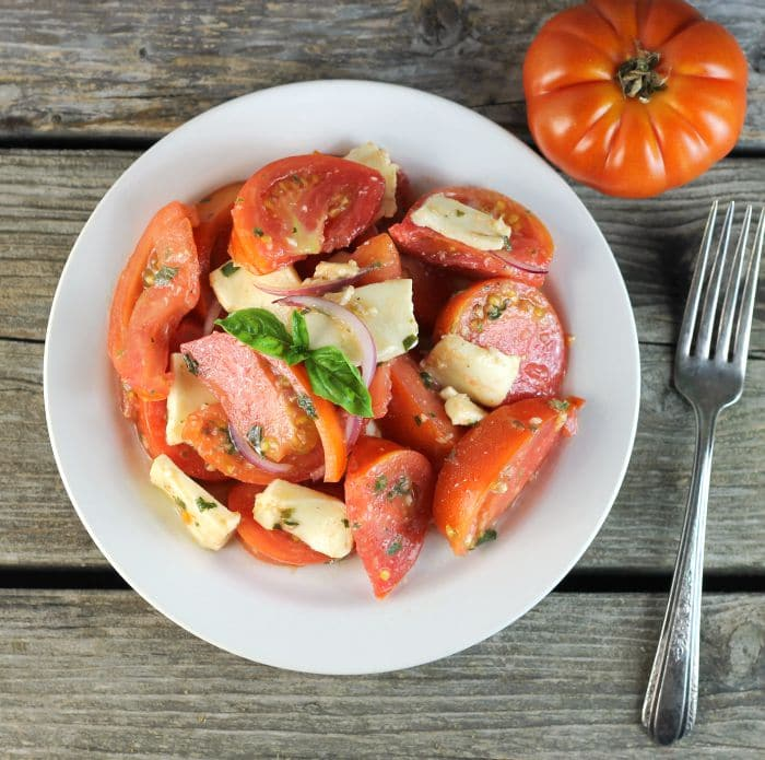 Tomato Mozzarella Salad made with tomatoes, mozzarella, and tossed with a vinaigrette dressing makes for a perfect end of the summer side dish.