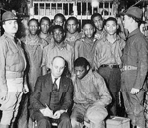 The nine Black teens, aged 12 to 18 — Haywood Patterson, Roy Wright, Andy Wright, Charlie Weems, Clarence Norris, Ozzie Powell, Willie Roberson, Olen Montgomery and Eugene Williams, (not named in order) meeting with their lawyer, attorney Samuel Leibowitz in 1931.Photo: Fred Hiroshige