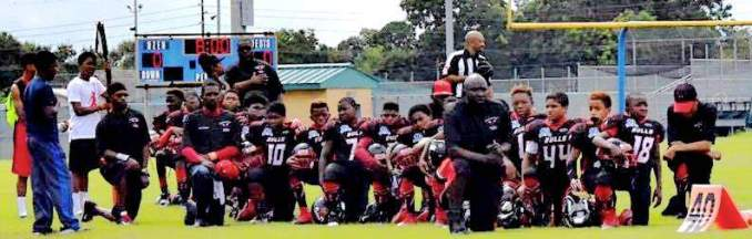 Beaumont Bulls team and coaches take a knee.