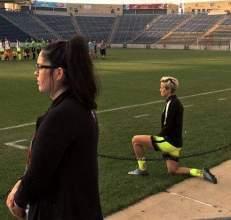 Megan Rapinoe kneeling.