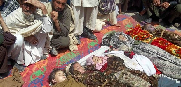 Afghan villagers sit near the bodies of children killed during a U.S.-led NATO airstrike in Kunar province on April 7, 2013.